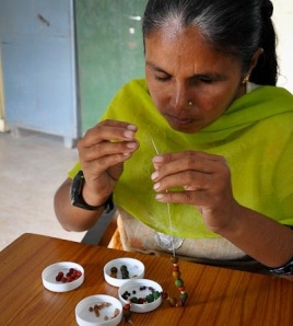 A crafts woman at work making scented jewellary