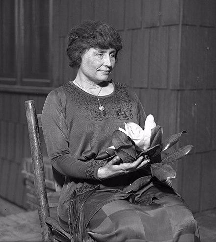 Helen Keller sitting holding a magnolia flower, circa 1920